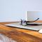 Lentes y computadora sobre mesa de madera