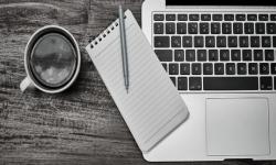 Escritorio de madera, taza de café, block de notas, lapicera y computadora con plano cenital.