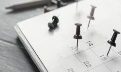 Hoja de calendario sobre mesa de madera con días señalados.