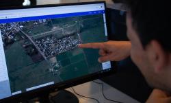 Geoportal persona indicando en la pantalla y otra observando. Se ve foto aérea.