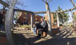 Juan y Alberto sentados en la plaza del complejo de viviendas