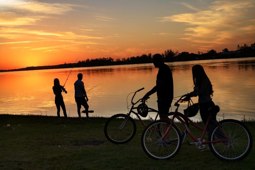 Atardecer en el lago con gente pescado y una pareja con sus bicicletas