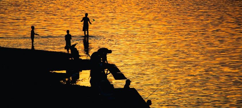 Personas pescando en un atardecer junto al río en Salto