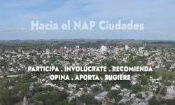 Fotografía de ciudad con texto sobreimpreso que dice Hacia el Nap Ciudadades