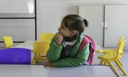 Niña sentada en un mesa en un jardín de infantes de la ANEP
