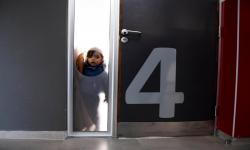 Niño espera dentro de un salón de un centro CAIF
