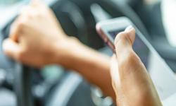 Imagen de una mano sosteniendo un teléfono celular mientras se conduce